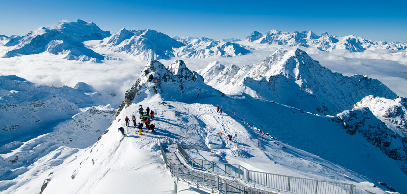 Switzerland_Verbier_skiers-summit-off-piste-drop-off.jpg